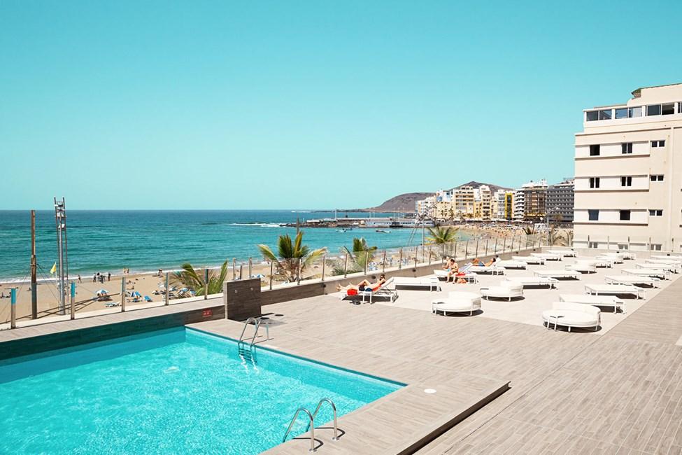 Hotellets solterrasse med pool og liggestole