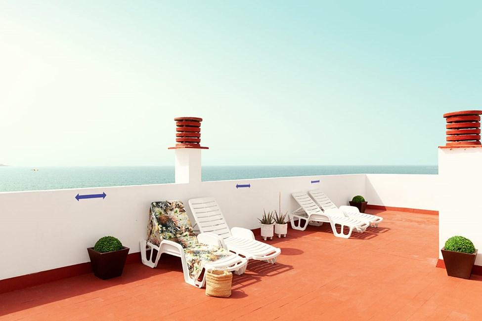 Hotellets tagterrasse med liggestole og fin udsigt over havet